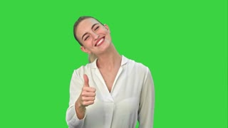 Happy excited woman showing approval hand gesture thumb up and smiling on a Green Screen, Chroma Key