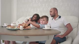 Happy family playing together while having breakfast at the restaurant table