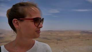 Happy female traveller enjoying desert view from cliff's edge
