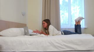 Happy woman lying on the hotel bed having video call via laptop