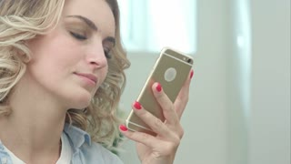 Happy young blond woman is sitting in a beauty salon and using a smartphone