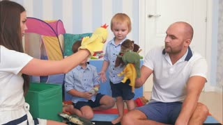 Happy young family playing animal hand puppets with their boys