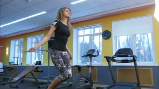 Healthy young woman jumping rope in a gym