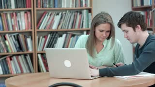 High school student working in library after classes, using laptop