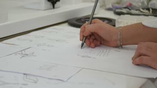 Jewelry designer s hand sketching out designs in studio