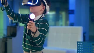 Little boy in virtual reality headset holding move motion controllers