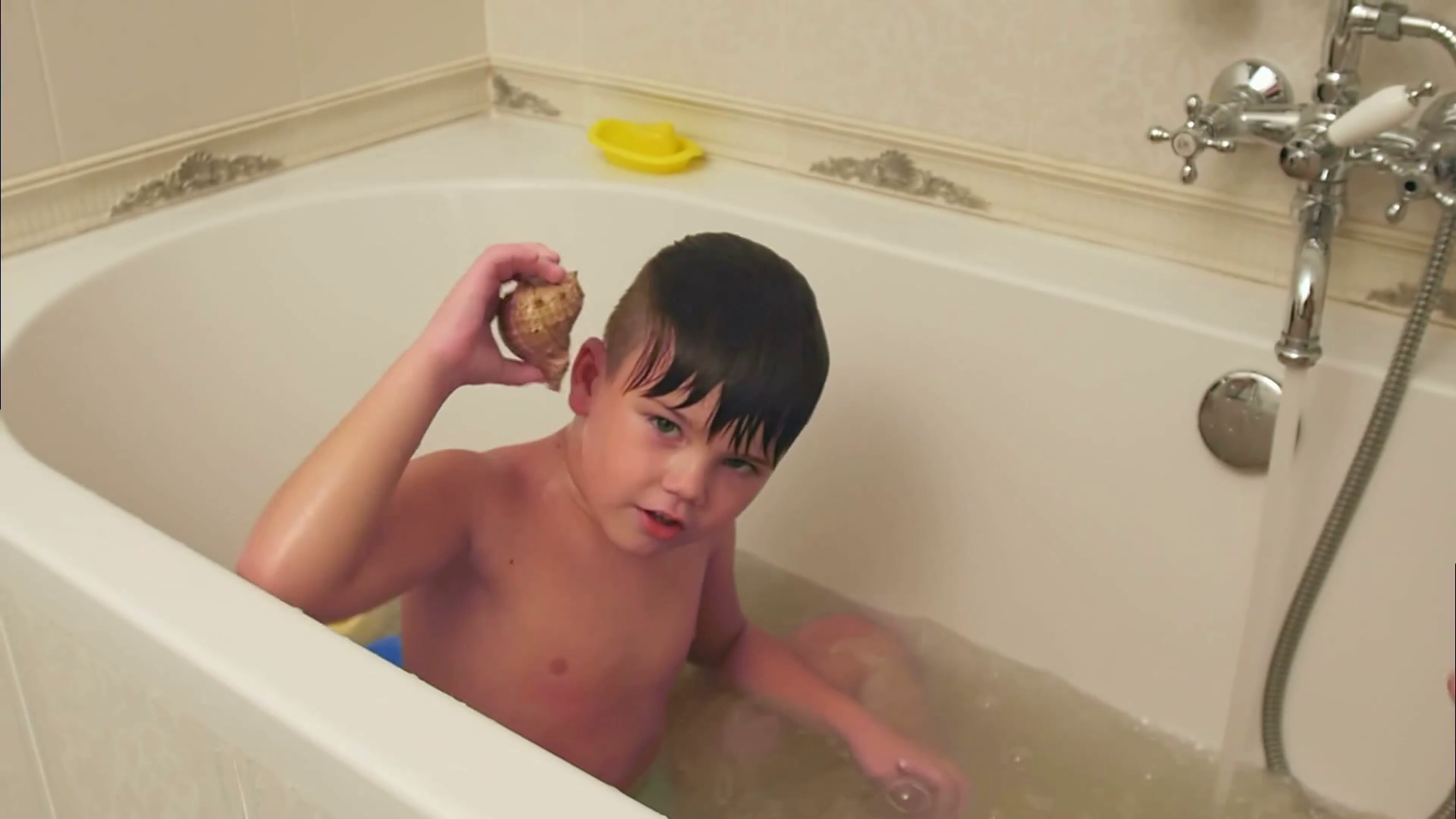 Little boy playing with seashell while taking bath in bathtub Stock Video Footage - Storyblocks