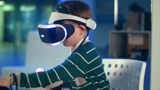 Little boy with virtual reality motion controllers having immersive gaming experience