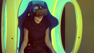 Little girl sitting in virtual reality attraction and feeling scary