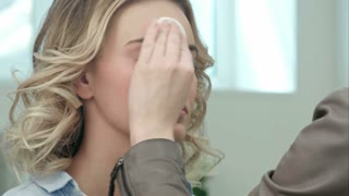 Make-up artist cleaning skin on model face