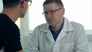 Male doctor in glasses consulting male patient