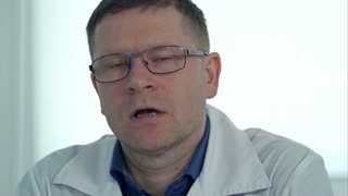 Male doctor in glasses talking to the camera