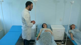 Male doctor talking to female patients on drip resting in hospital ward