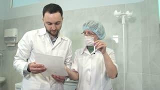 Male doctor talking to nurse holding blood sample