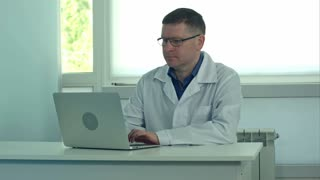 Male doctor working on laptop computer on white desk in hospital