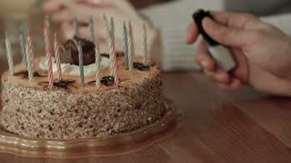 Male hand lighting candles in birthday cake