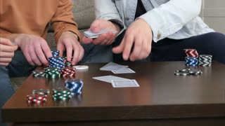Male hands give out cards on the table in the living room
