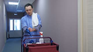 Male hotel cleaner putting on gloves before cleaning the room
