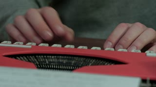 Male's hands typing on a red typing machine