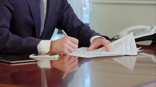 Man hand signs a paper document with ballpoint pen. Signature is fake