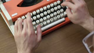 Man's hands typing on an old red mechanical typewriter