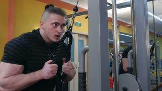 Muscular body builder working out at the gym on a cable machine