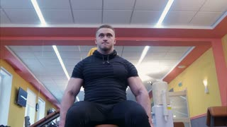 Muscular bodybuilder doing exercises with dumbbells in gym