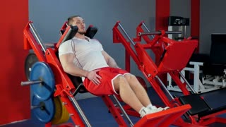 Muscular man doing legs exercise on the gym equipment
