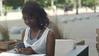 Nice african american girl with dark hair using smartphone and taking order in outside restaurant