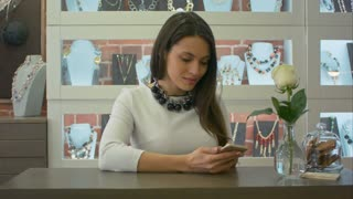 Nice female seller texting messages on smartphone and cute smiling in a jewelry store