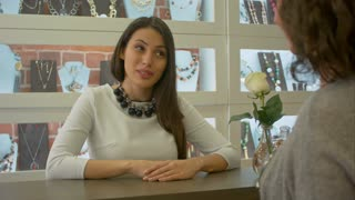 Nice seller consultant offers to choose some jewellery to a customer in a jewelry store