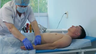 Nurse performing electrocardiography on a male patient