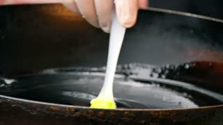 Oiling the frying pan using the silicone brush