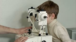 Old male doctor examines eyes of boy through slit lamp