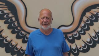 Old man standing in front of wings wall graffiti