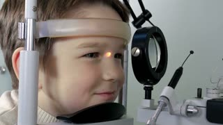 Optometrist performing visual field test of young boy