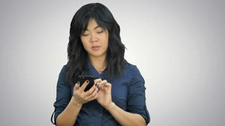 Pensive asian businesswoman reading presentation on smartphone, looking at camera on white background