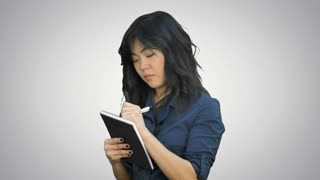 Pensive asian woman makes some notes in notepad on white background