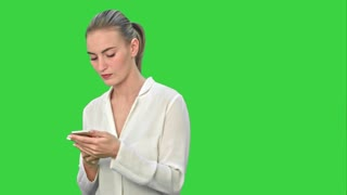 Pensive business woman using mobile cell phone reading message, wear white suit on a Green Screen, Chroma Key