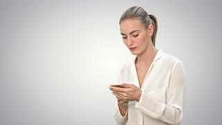 Pensive business woman using mobile cell phone reading message, wear white suit on white background