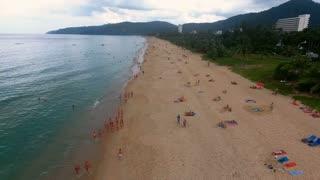 PHUKET, THAILAND - 20 JAN 2017: Flying over empty beach and few people walking and having sunbath on the beach