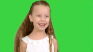Playing, jumping little girl in white dress enjoys game on a Green Screen, Chroma Key