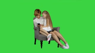 Pleasant smiling mother and daughter using cell phone on a Green Screen, Chroma Key