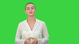 Portrait of a young business woman presenting something by a hand on a Green Screen, Chroma Key