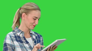 Portrait of a young woman using a tablet on a Green Screen, Chroma Key