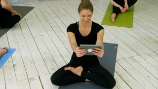 Portrait of smiling fit woman using digital tablet having video chat while sitting at yoga mat after fitness workout