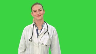 Portrait of young medical doctor woman smiling, giving thumbs up hand sign, looking at camera with stethoscope and lab coat on a Green Screen, Chroma Key