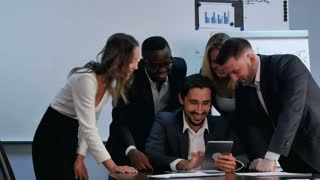 Positive business people working with digital tablet in office