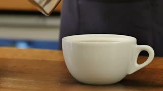 Pouring coffee into cup with milk