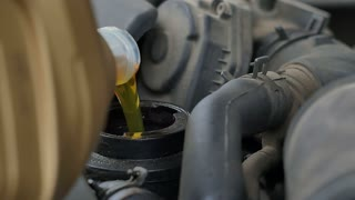 Pouring oil to car engine